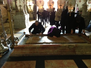 Pilgrims bowing before the stone that held Christ's body