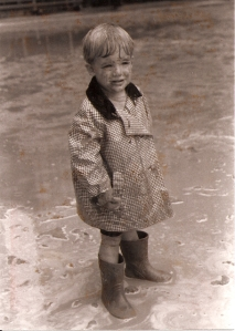 Middle Man as a little man, in his favorite red boots, his dad's old rain jacket and a mud puddle.
